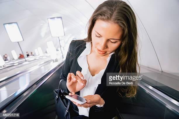 美しい女性彼女のスマートフォンを使用しながら、エスカレーター