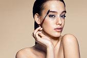 Beautiful woman using mascara / photos of appealing brunette girl on beige background