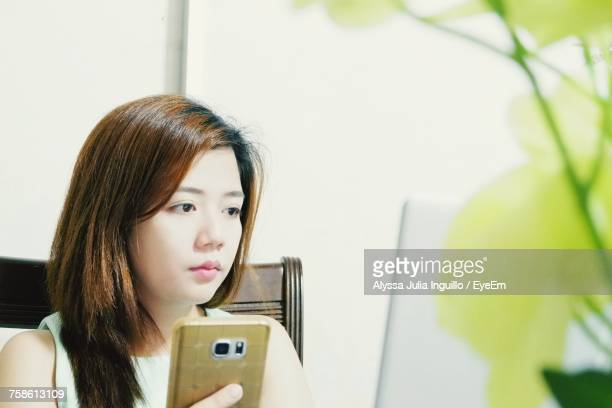 Beautiful Woman Using Phone And Laptop While Sitting On Chair
