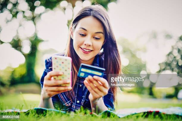 Beautiful woman using smart phone and credit card in park