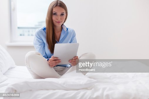 Beautiful woman using tablet computer on her bed : Stock Photo