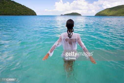 Beautiful woman wading in serene water