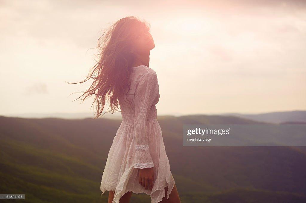A beautiful woman walking around a mountainside