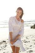 Portrait of a beautiful woman walking on beach with sun dress