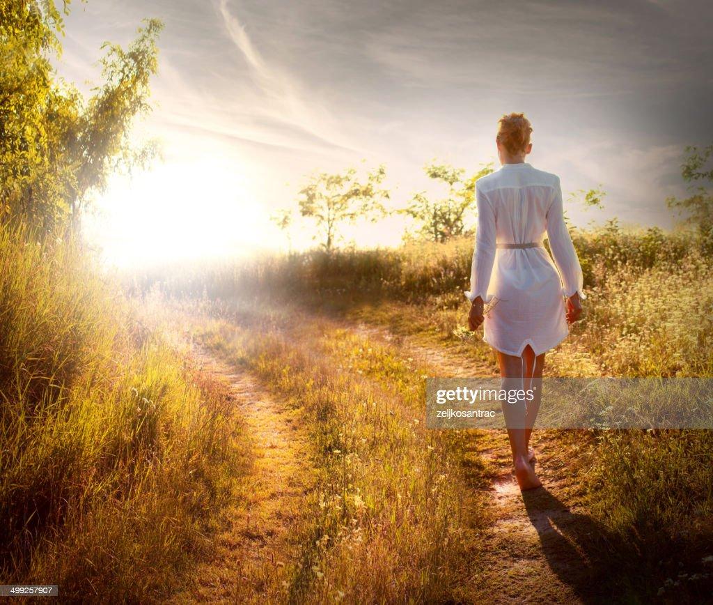 Beautiful woman walking on the field
