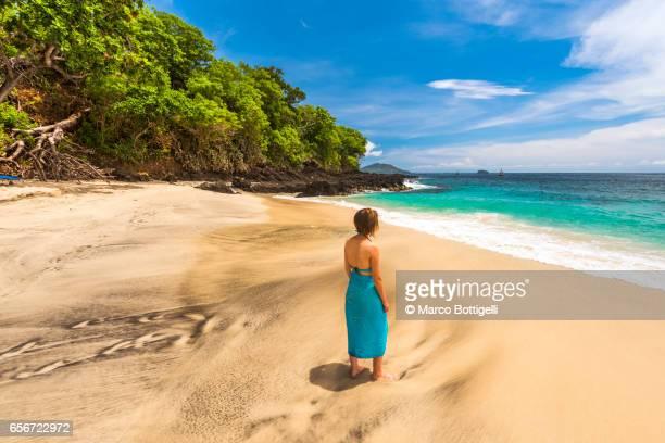A beautiful woman walking on the tropical beach of White Sand Beach (Bias Tugel). Bali.