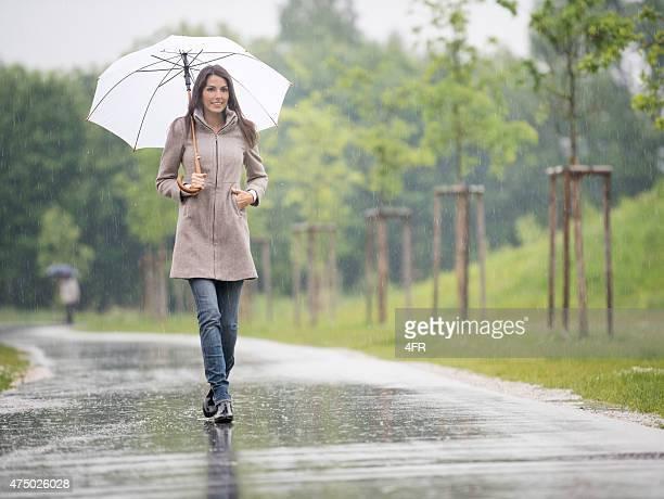 Schöne Frau zu Fuß unter Ihren Regenschirm im Regen