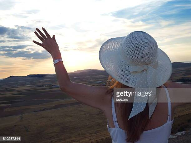 Beautiful woman watching from a viewpoint you the aterdecer in fields of Castilla