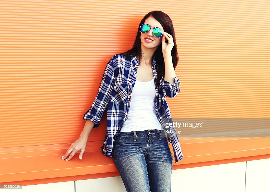 Schöne Frau Tragen einer Sonnenbrille und über farbenfrohe Kariertes Hemd : Stock-Foto