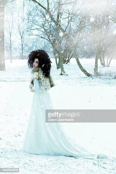 Schöne Frau mit einem Brautkleid im Schnee