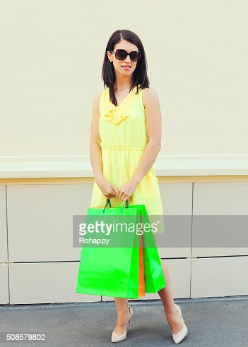 Beautiful woman wearing dress with shopping bags in city : Stockfoto