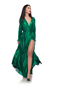 beautiful brunette woman wearing a green gown stepping on white background and looking to side, full length picture