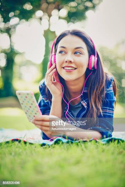 Beautiful woman wearing headphones while holding smart phone in park