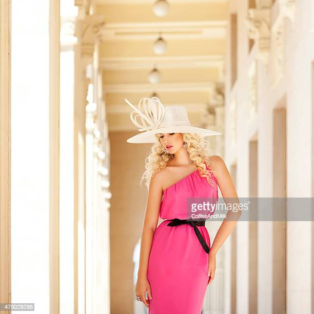 Beautiful woman wearing summer hat and pink dress haute couture