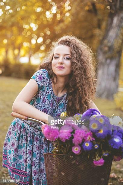 Schöne Frau mit einem Korb voller Blumen
