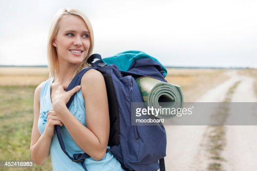 Beautiful woman with backpack looking away while hiking at field : Stock-Foto