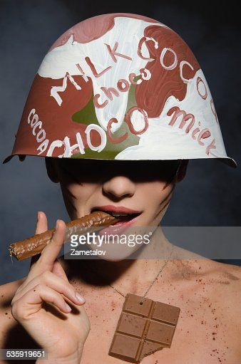 Beautiful woman with chocolate cigar in hand and helmet : Stock Photo