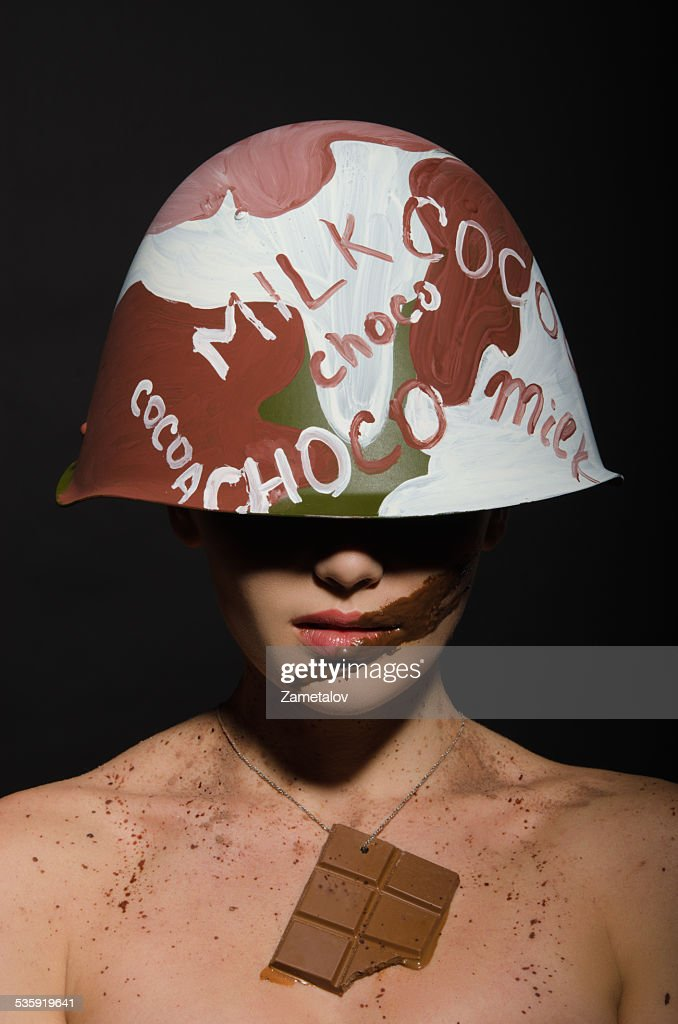 Beautiful woman with chocolate helmet, camouflage and badge : Stock Photo