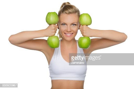 Beautiful woman with dumbbells of green apples : Stock Photo