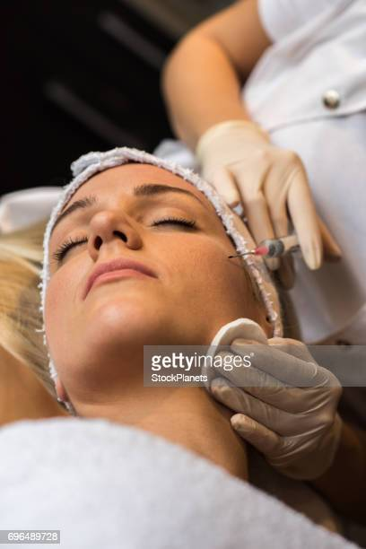 Beautiful woman with eyes closed receiving Botox injection.