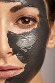 Beautiful woman with facial mask having her eyes closed