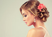 Beautiful woman with colorful makeup and fashion wedding hairstyle. Rose flowers in the hair.