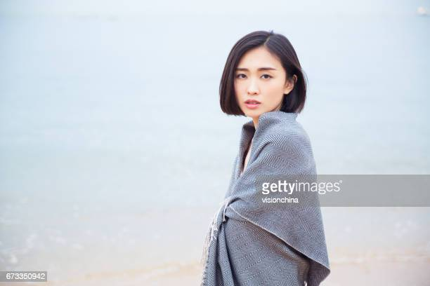 Beautiful woman with grey scarf standing on beach