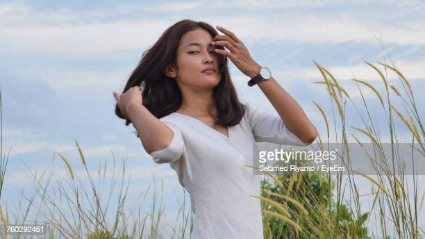 Beautiful Woman With Hands In Hair Standing On Grassy Field Against Sky
