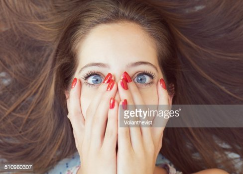 Beautiful woman with hands on face and red nails : ストックフォト