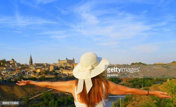 Beautiful woman with hat happily observing the ancient city of Toledo