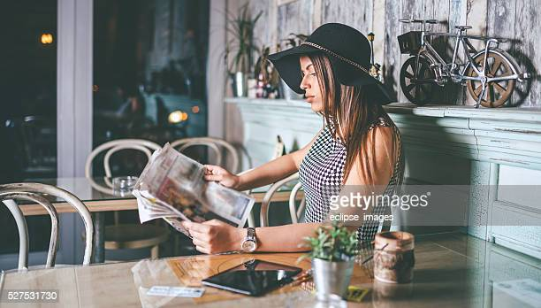 Linda mulher com chapéu de ler jornais