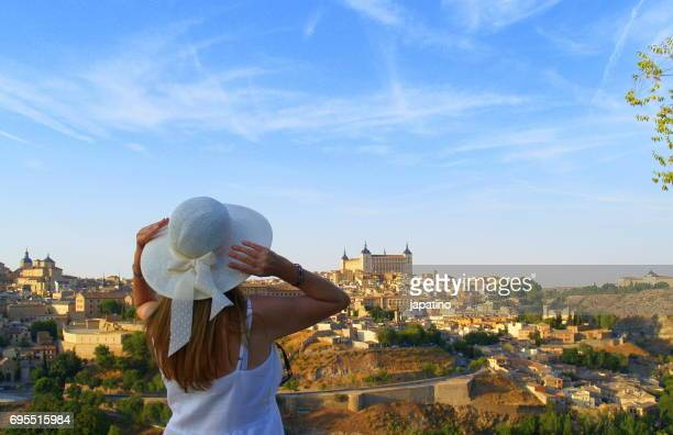 Beautiful woman with hat watching the city of Toledo