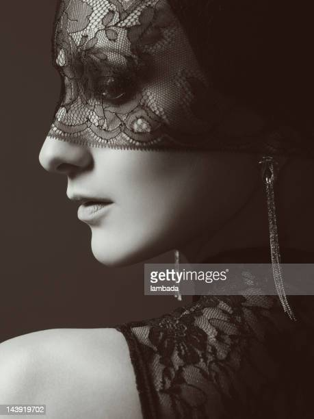 Beautiful woman with lace mask over her eyes
