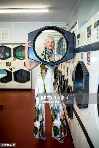 Beautiful woman with long, silvery, grey hair in her late fifties wearing a modern, colorful outfit inside a laundromat.