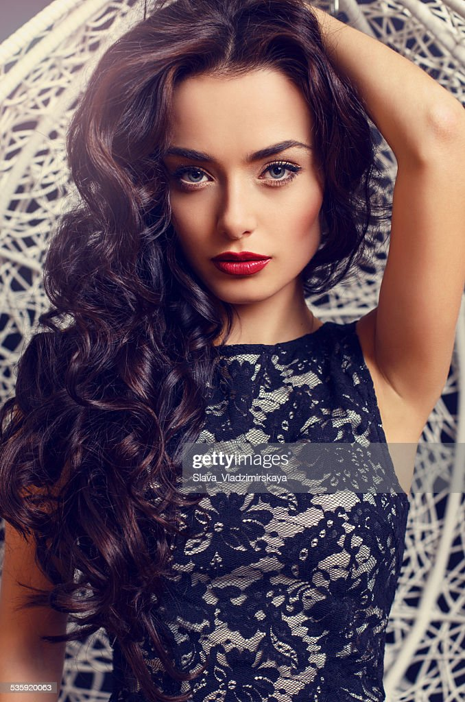 beautiful woman with luxurious dark hair in lace dress : Stock Photo
