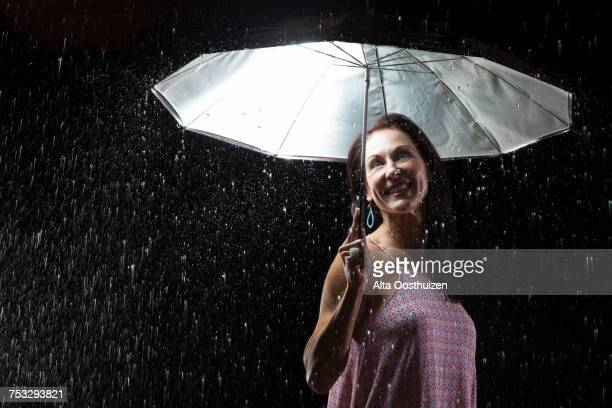 Beautiful woman with pink dress under an umbrella at night - Studio, South Africa