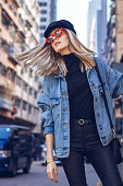A beautiful young blond woman with fashionable red sunglasses walking through a small urban street in Hong Kong. She is dressed in black clothes with a denim jacket and dancing on the street.