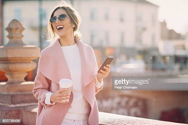 Beautiful woman with smart phone at sunlight