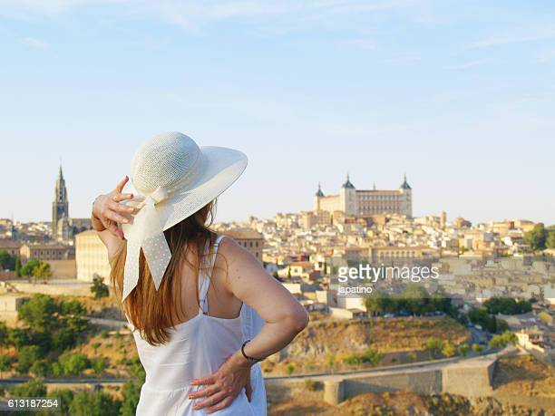 Beautiful woman with straw hat watching the city of Toledo from a lookout on the outskirts of the city