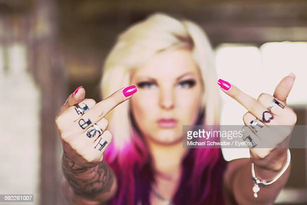 Beautiful Woman With Tattooed Hands Giving Obscene Gesture