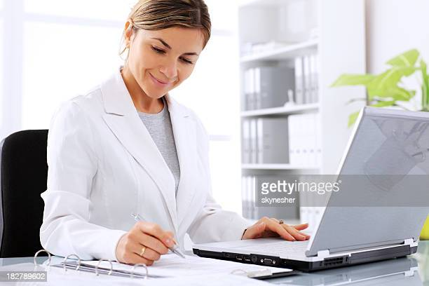 Beautiful woman working on laptop in the office.