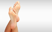 Beautiful woman's bare feet against a grey background with copyspace