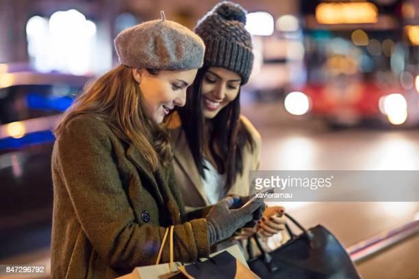 Schöne Frauen, die Überprüfung von Handy auf der Straße nach dem Einkaufen in der Stadt in der Nacht