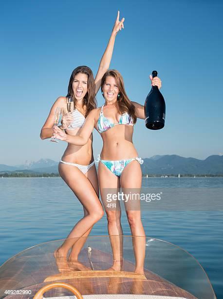 Schöne Frau trinkt Champagner auf einem Boot Deck