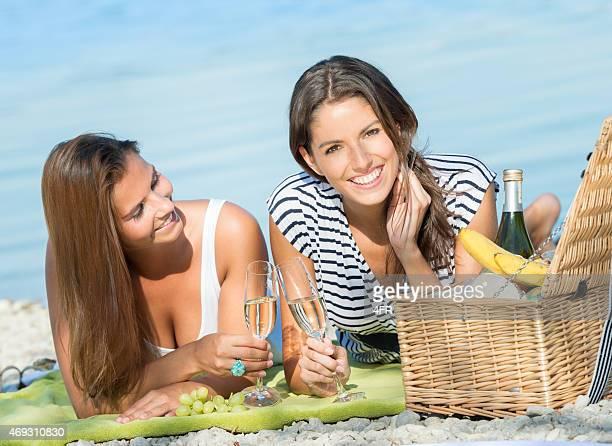 Schöne Frauen mit einem Picknick am See