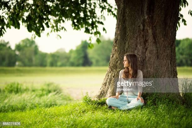 Belles femmes reposantes sous un arbre de châtaigne