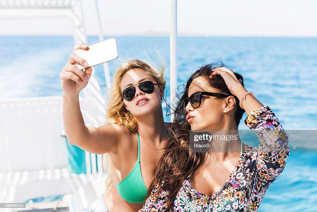 Beautiful women taking a selfie on boat. : Stock Photo