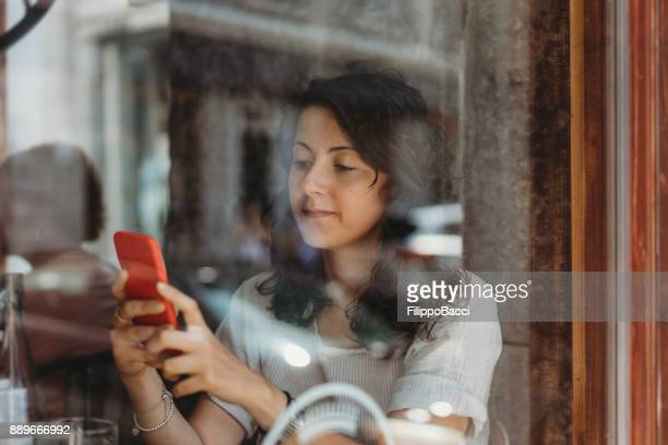 Beautiful young adult woman drinking at café
