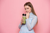 Beautiful young adult woman drinking healthy green smoothie cocktail near pink wall