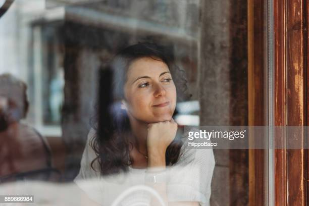 Beautiful young adult woman looking out of the window